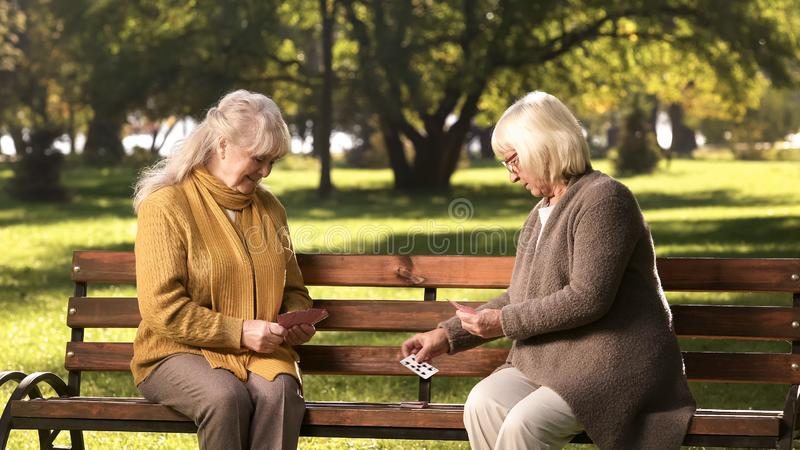 Mature lady making attack, playing cards game with friend, sitting on bench royalty free stock image