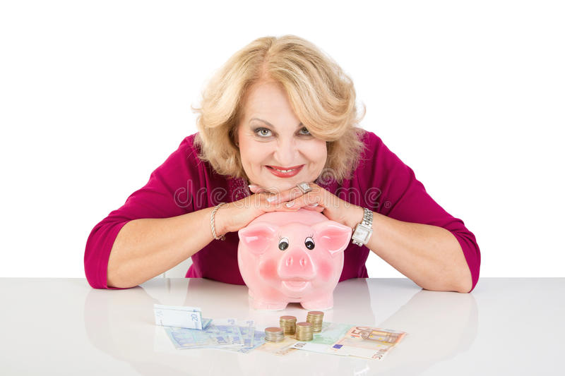 Mature lady with piggy bank - woman isolated on white background stock images