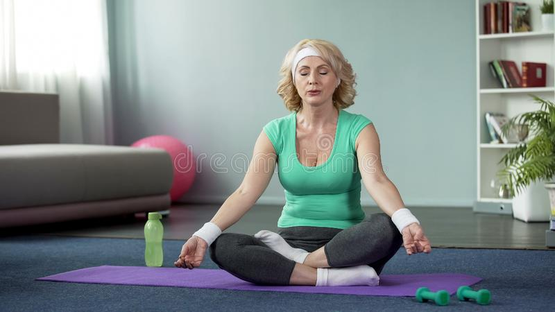 Mature lady practicing yoga at home, doing relaxation exercises, meditation stock images