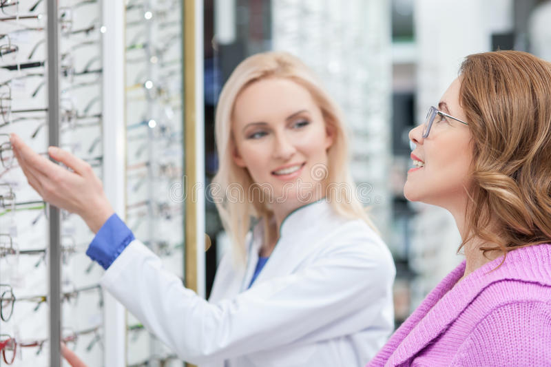 Mature lady is ready to buy eyeglasses. Cheerful senior women is choosing new spectacles with the help of optician. She is standing and smiling stock photography