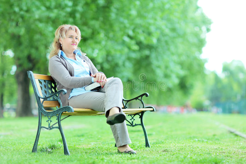 Mature lady relaxing in a park seated on a bench royalty free stock photography