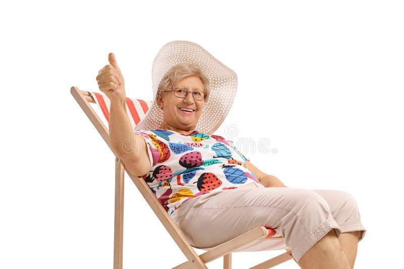 Mature lady seated in a deck chair making a thumb up sign stock image