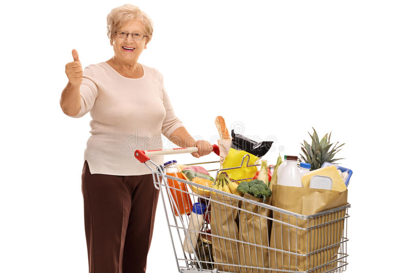 Mature lady with shopping cart giving thumb up. Cheerful mature lady with a shopping cart full of groceries giving a thumb up isolated on white background royalty free stock photo