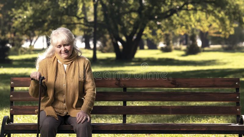 Mature lady with walking stick resting on park bench during promenade loneliness stock photo