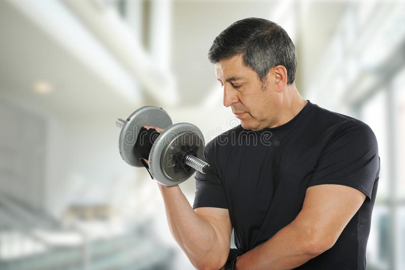 Mature latin man working out. With weights indoors and wearing a black shirt stock images