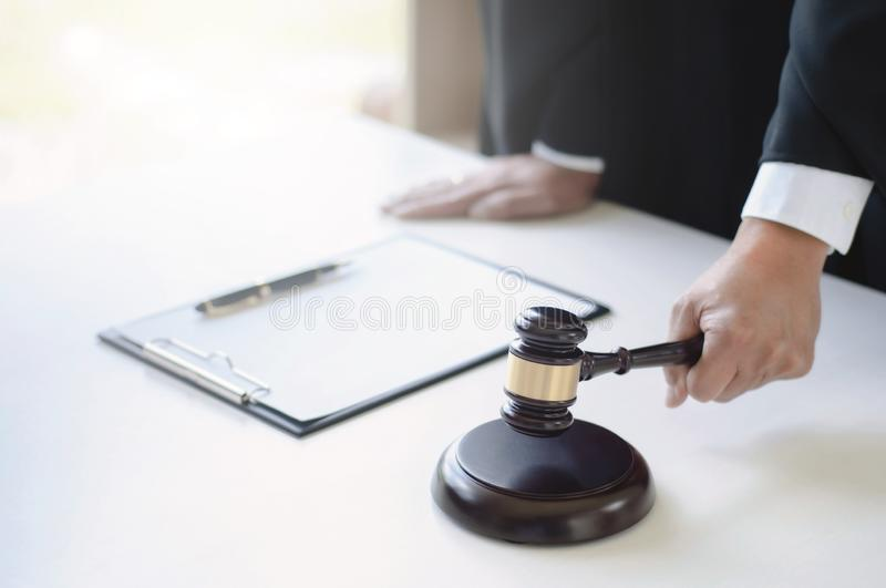 Mature lawyer working at courtroom with justice hammer on hand.  royalty free stock image