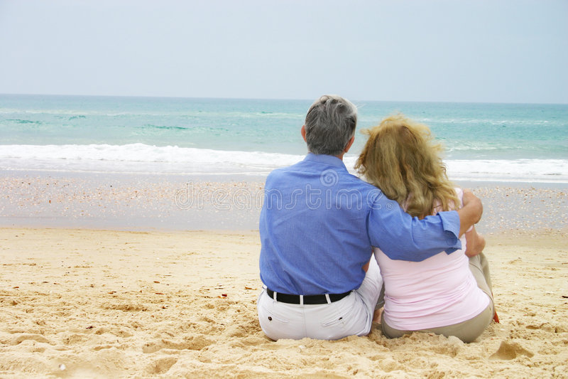 Mature love. Mature couple having a sitting in the sand stock images