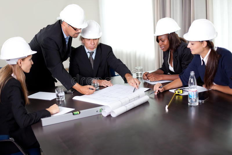 Mature male architect explaning his colleagues stock image