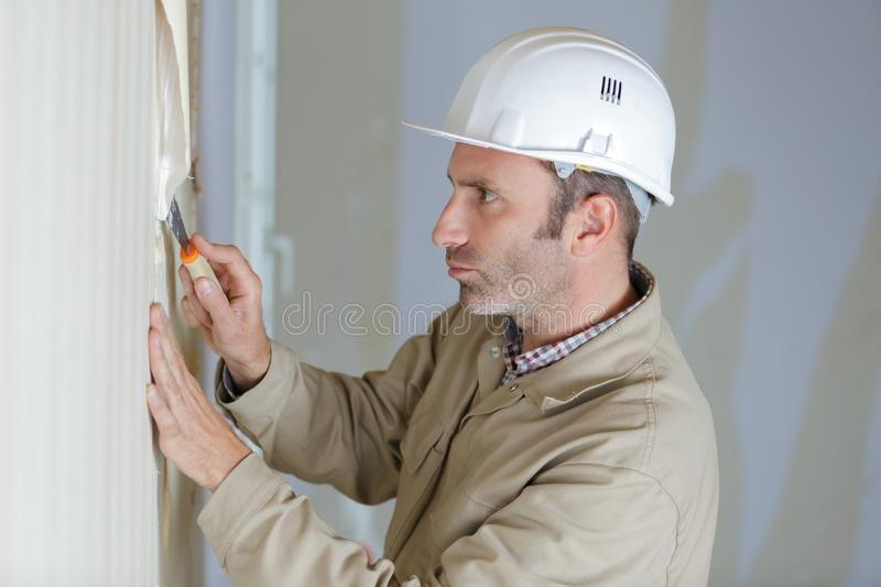 Mature male builder stripping wallpaper with scraper stock image