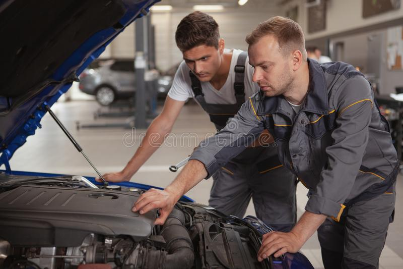Two male mechanics working at the garage. Mature male car mechanic helping his younger colleague repairing broken automobile. Two car service technicians looking stock images