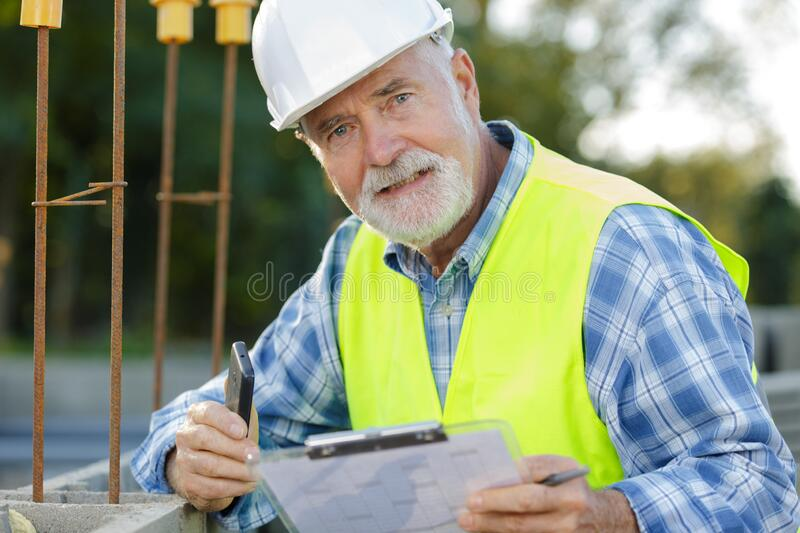 Mature male civil engineer wearing protective vest and helmet royalty free stock photography