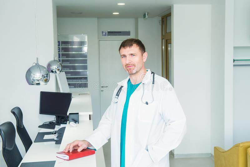 Mature male confident Doctor`s portrait standing at hospital reception desk in the hall of the modern medical clinic. Health care stock photos