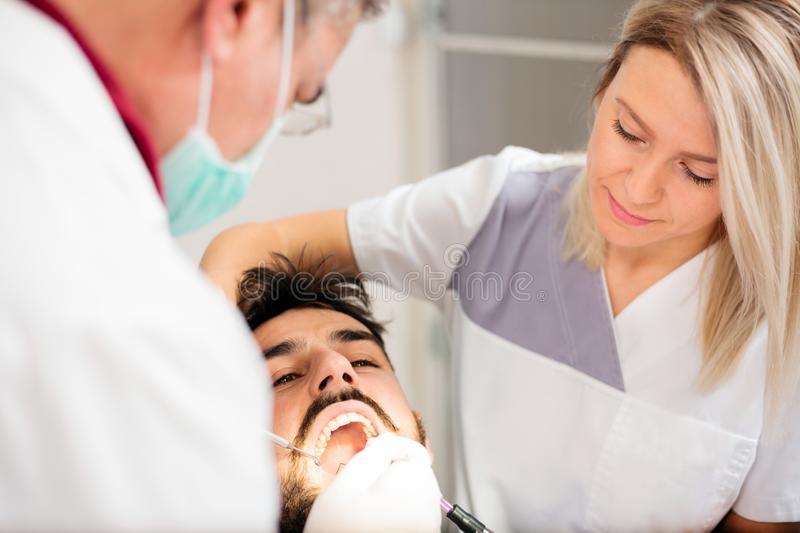 Mature male dentist and beautiful young female assistant performing dental exam on a young male patient in dental clinic stock photo