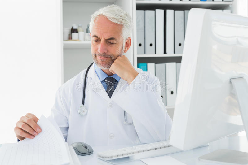 Mature male doctor with computer at medical office stock photography