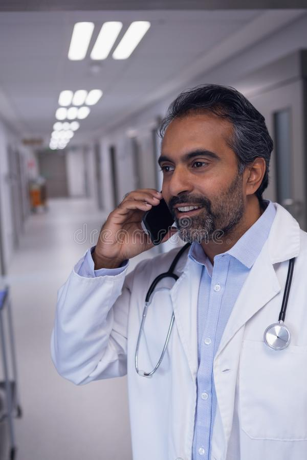 Mature male doctor talking on mobile phone in hospital corridor. Front view of mature mixed race male doctor talking on mobile phone in hospital corridor royalty free stock images