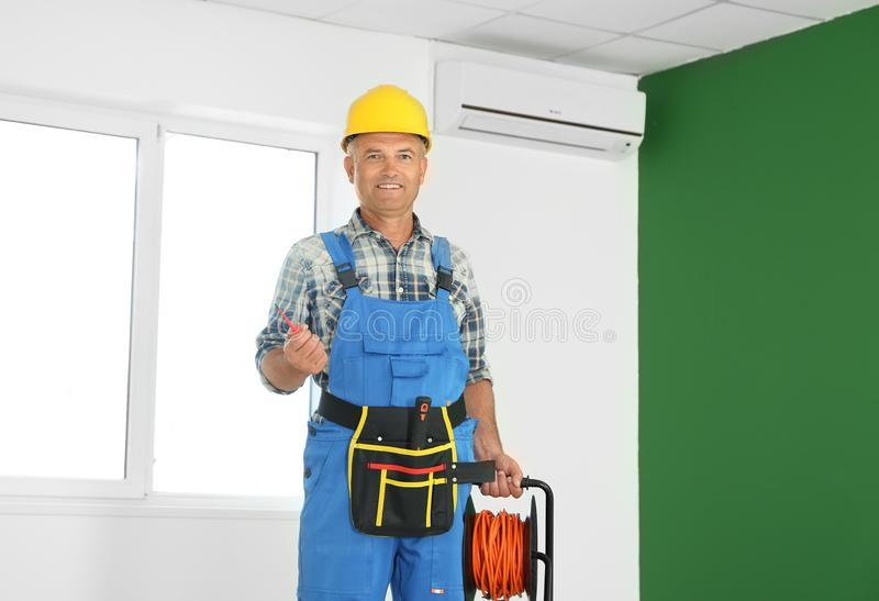 Mature male electrician with extension cord reel in empty flat stock images