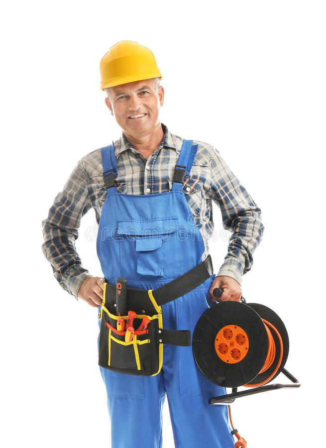 Mature male electrician with extension cord reel on white background stock images