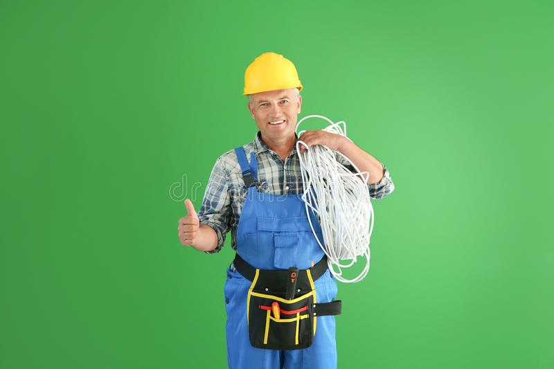 Mature male electrician showing thumb-up gesture on color background stock images