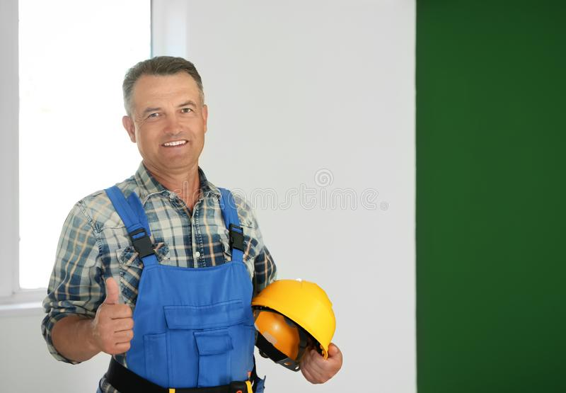 Mature male electrician showing thumb-up gesture in empty flat stock photo