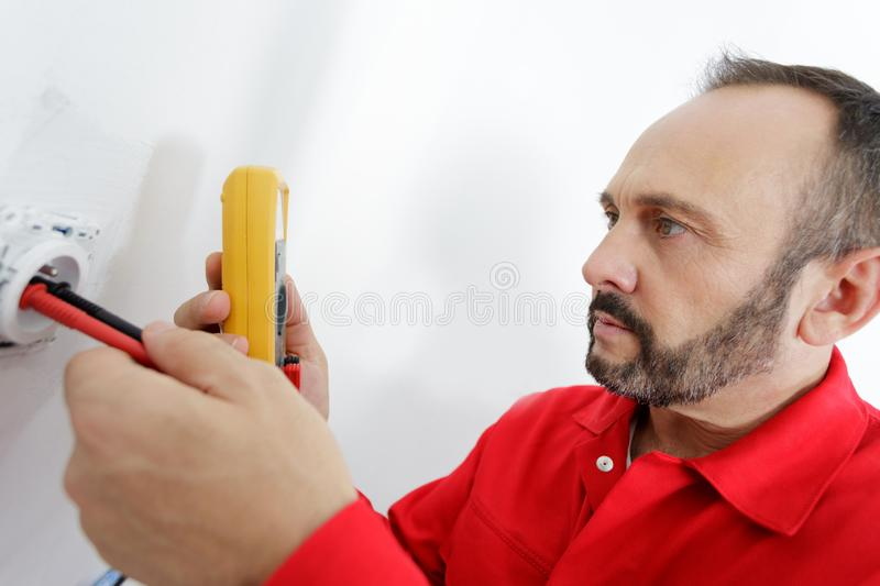 Mature male electrician testing socket with multimeter. Electrician stock images