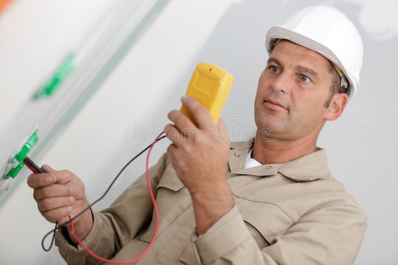 Mature male electrician using multimeter stock photo