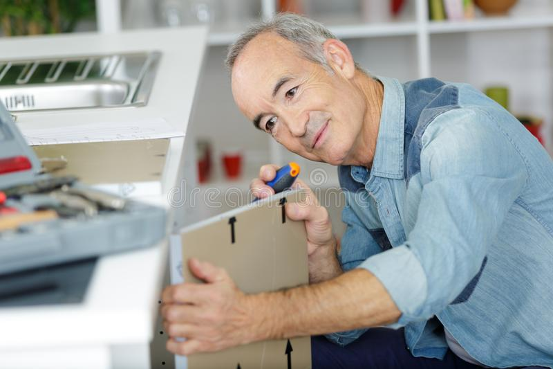 Mature male fitting door onto kitchen cupboard stock images