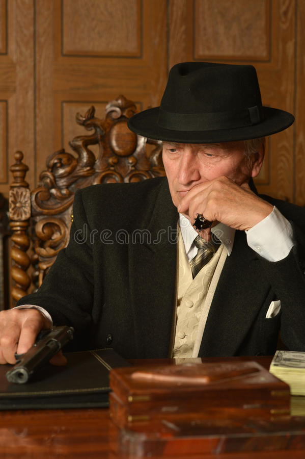 Mature male mafia boss. On the table with gun royalty free stock photography