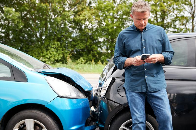 Mature Male Motorist Involved In Car Accident Calling Insurance Company Or Recovery Service stock photos