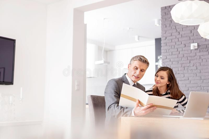 Mature male realtor and female buyer reading document while sitting at table in apartment royalty free stock image