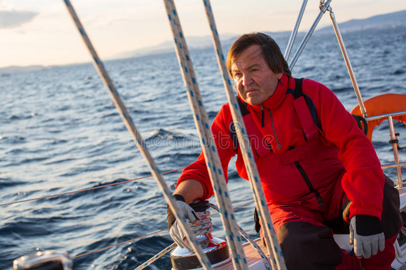 Mature male skipper sitting on his sailing yacht. Sport. royalty free stock images