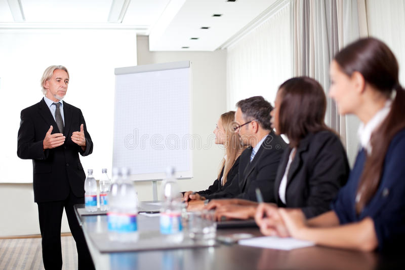 Mature male speaker giving presentation stock photos