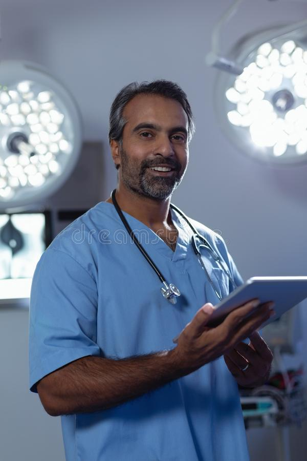 Mature male surgeon looking at camera while using digital tablet in operation room at hospital stock image