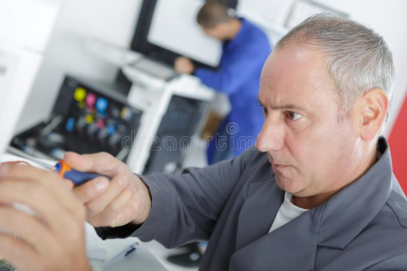 Mature male technician checking fridge with digital multimeter at home stock images