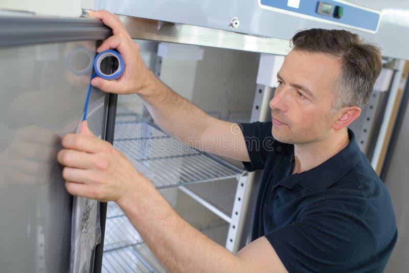Mature male technician measuring fridge stock photography