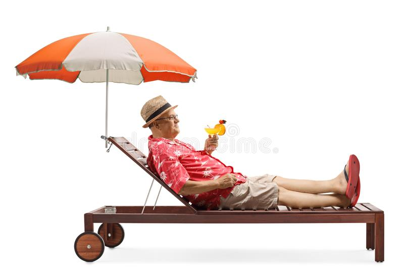 Mature male tourist holding a cocktail and relaxing under umbrella stock photo