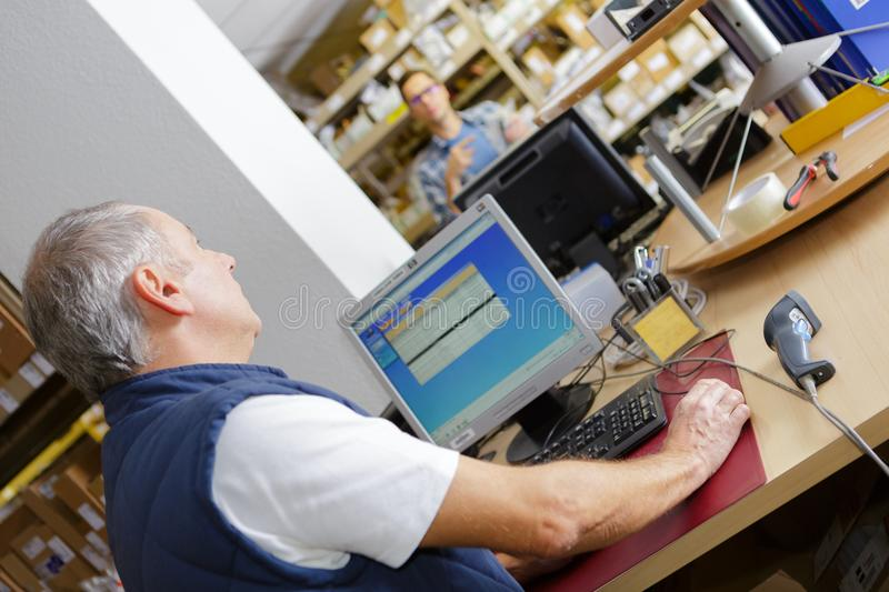 Mature male worker at computer workstation stock photo