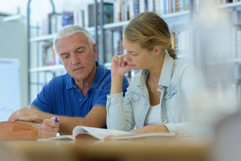 Mature male and young girl in library royalty free stock image