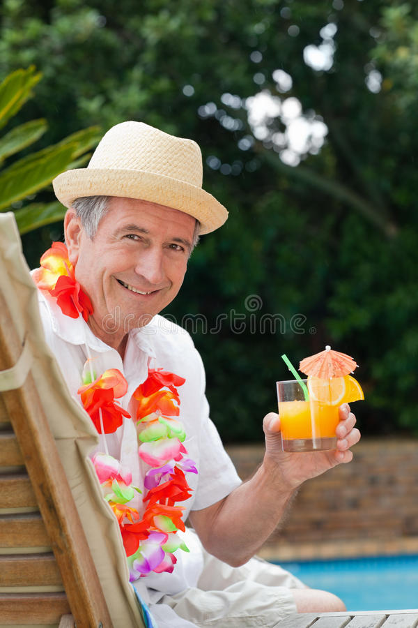 Mature man. Drinking a cocktail beside the swimming pool royalty free stock photography