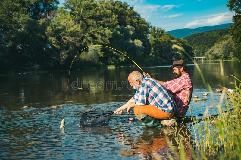 Mature man with adult son fishing. Fisher masculine hobby. Successful fly fishing. Cheerful mature fisherman fishing in royalty free stock images