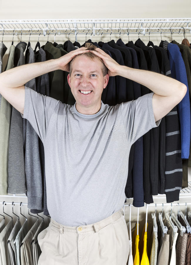 Mature man anger while dressing. Vertical portrait of mature Caucasian man in walk-in closet showing frustration with hands behind head while pulling his hair stock photo
