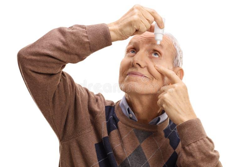 Mature man applying eye drops royalty free stock photo
