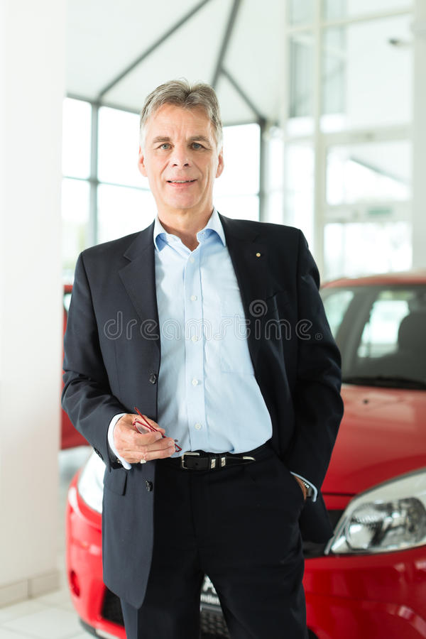 Mature man with auto in car dealership. Mature single man with red auto in light car dealership, he is obviously buying a car or is a car dealer stock photos