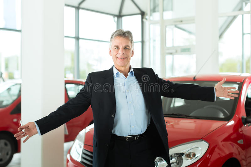 Mature man with auto in car dealership. Mature single man with red auto in light car dealership, he is obviously buying a car or is a car dealer royalty free stock image