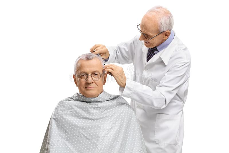 Mature man with a barber cutting his hair royalty free stock image