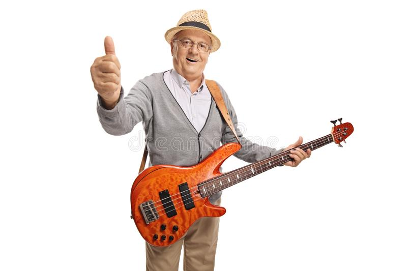 Mature man with a bass guitar showing thumb up royalty free stock images