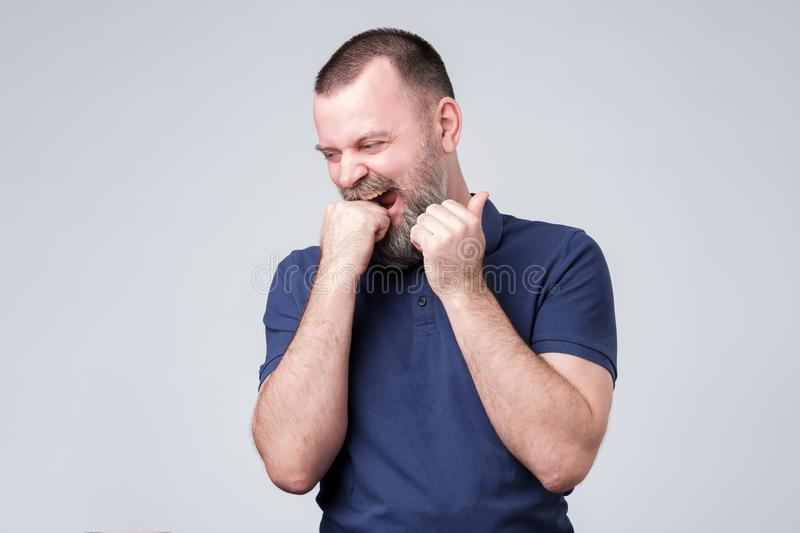 Mature man with beard bites fist feeling nervous. Mature man with beard in blue t-shirt bites fist feeling nervous. Negative facial emotion stock photo