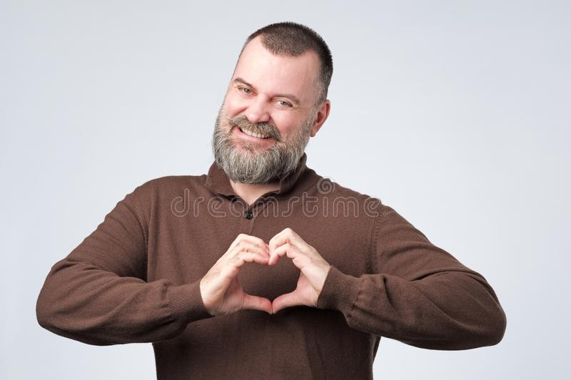 Mature man with beard making out of the hands heart. royalty free stock image