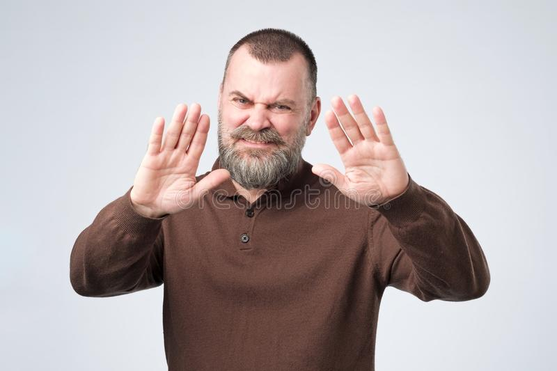Mature man with beard shows refusal gesture, does not want to speak with you stock image