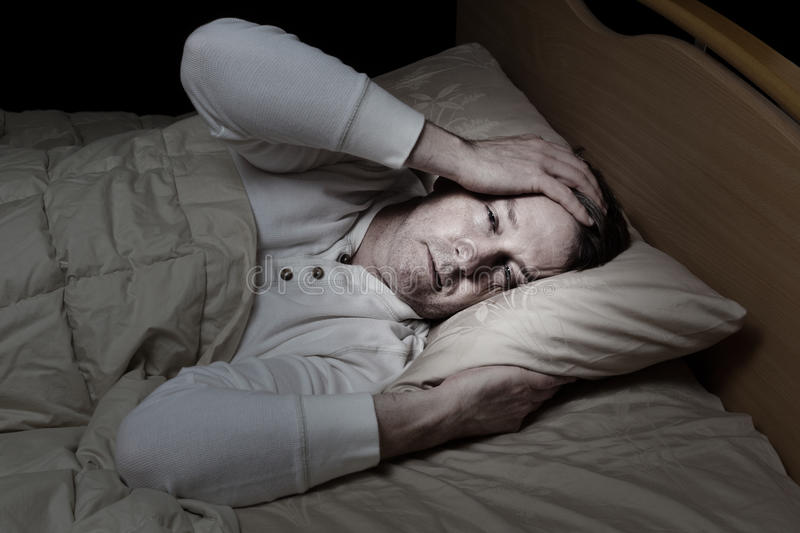 Mature man in bed very sick. Horizontal image of sick mature man, holding his head, while in bed stock photography