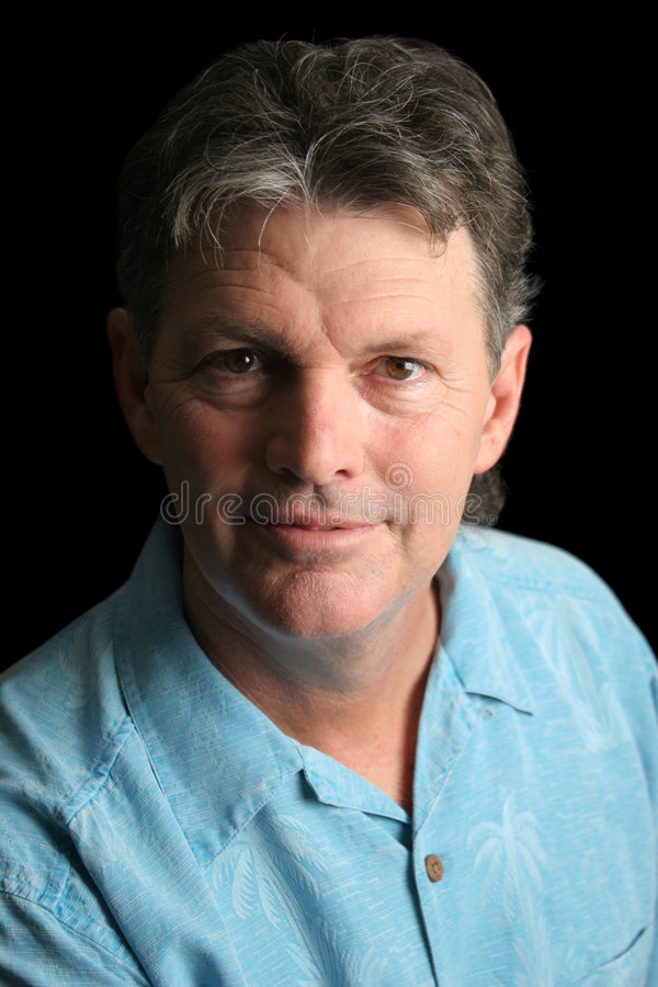 Mature Man on Black - Kind. A handsome, mature man over a black background with dramatic side light stock photos